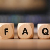 """Three wooden cubes, each with a letter """"F"""", """"A"""" and """"Q"""" printed on it, stand on a table."""